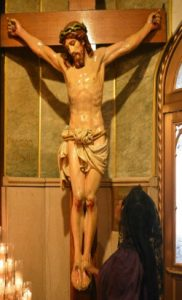 kneeling at foot of cross, crucifix at Holy Innocents Church